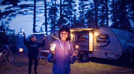 Roulotte Prolite sur un terrain de camping en soirée avec des enfants qui jouent dehors